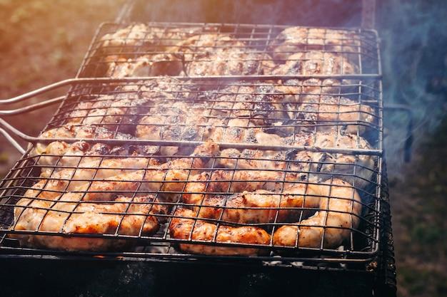 Saucisses, le poulet est cuit sur le gril. processus de cuisson d'un barbecue avec de la fumée