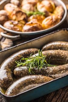 Saucisses rôties dans une poêle avec du romarin et des pommes de terre.. cuisine européenne traditionnelle bratwurst jaternice ou jitrnice.