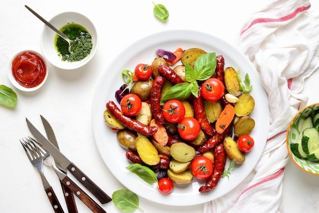 Saucisses rôties avec pommes de terre et servies avec trempette verte épicée saine et ketchup aux tomates