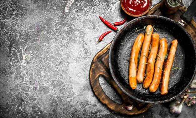 Saucisses à la sauce tomate sur le plateau. sur un fond rustique.