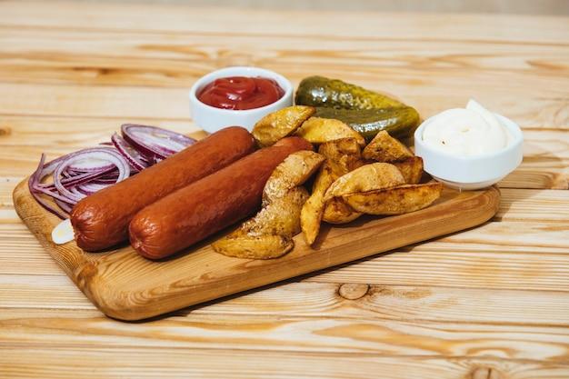 Saucisses avec sauces aux pommes de terre au four, oignons et cornichons sur une planche en bois sur la table