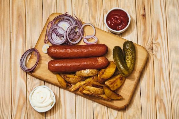 Saucisses avec sauces aux pommes de terre au four, oignons et cornichons sur une planche de bois sur la vue de dessus de table