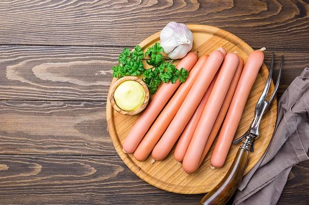 Saucisses de saucisses crues avec sauce sur une planche à découper sur une surface en bois