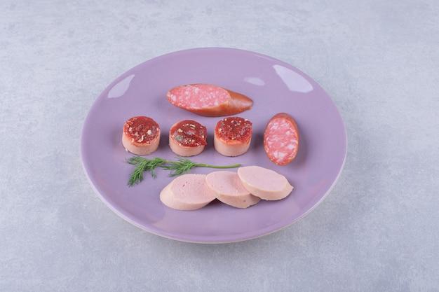 Saucisses savoureuses bouillies et fumées sur plaque violette.
