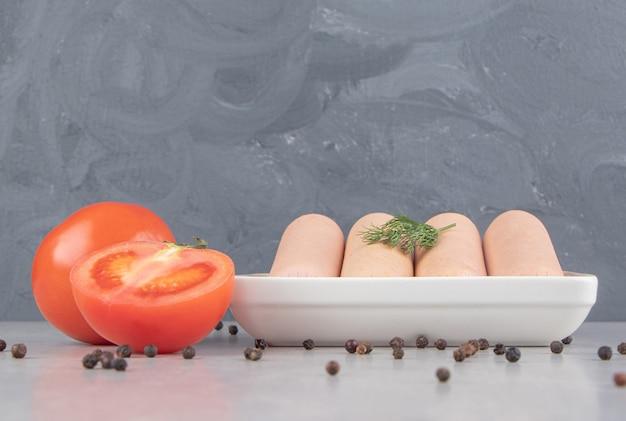 Saucisses savoureuses bouillies sur une plaque blanche avec des tomates.