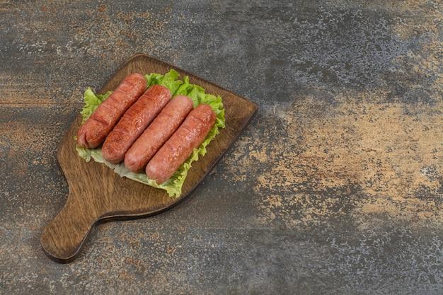 Saucisses savoureuses grillées sur planche de bois.