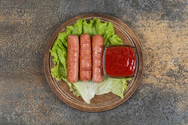 Saucisses savoureuses rôties et ketchup sur planche de bois.