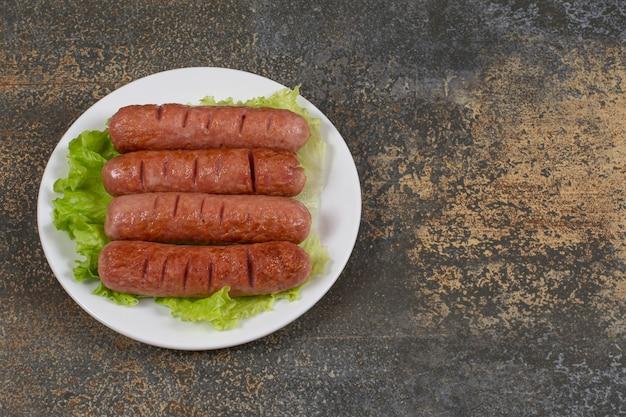 Saucisses savoureuses rôties avec de la laitue sur une plaque blanche.