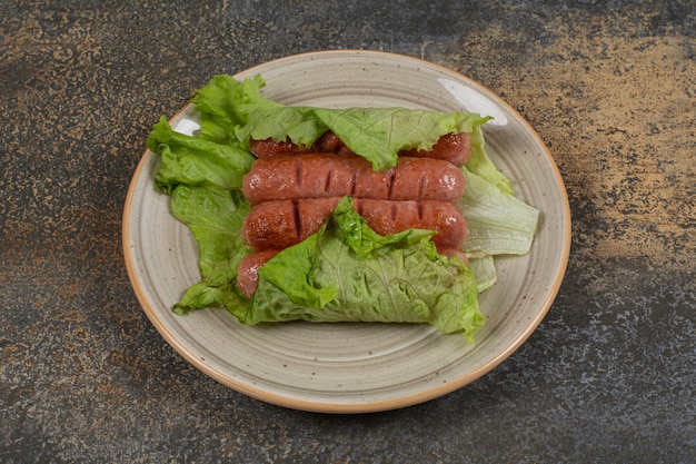 Saucisses savoureuses rôties sur plaque en céramique.