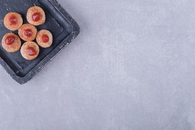 Saucisses tranchées avec du ketchup sur tableau noir.