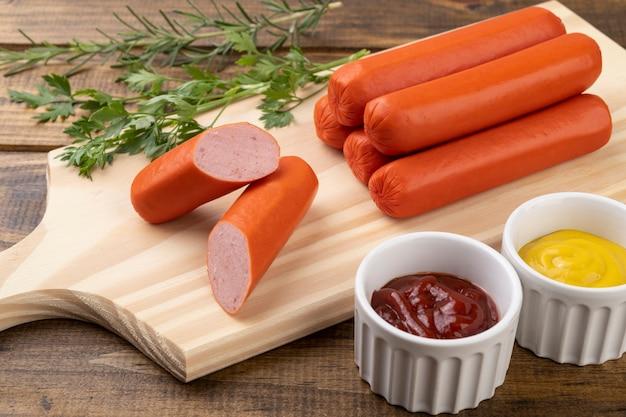 Saucisses et tranches sur une planche de bois avec du ketchup et de la moutarde.