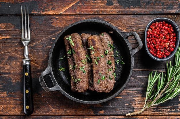 Saucisses de viande hachée grillées dans une poêle.