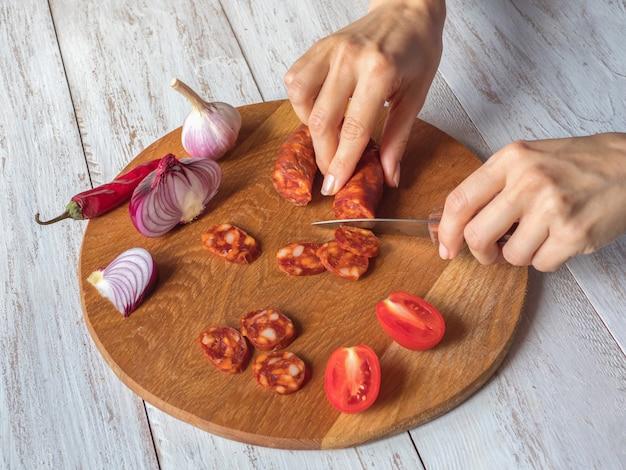Le saucisson chorizo est tranché sur une planche à découper en bois
