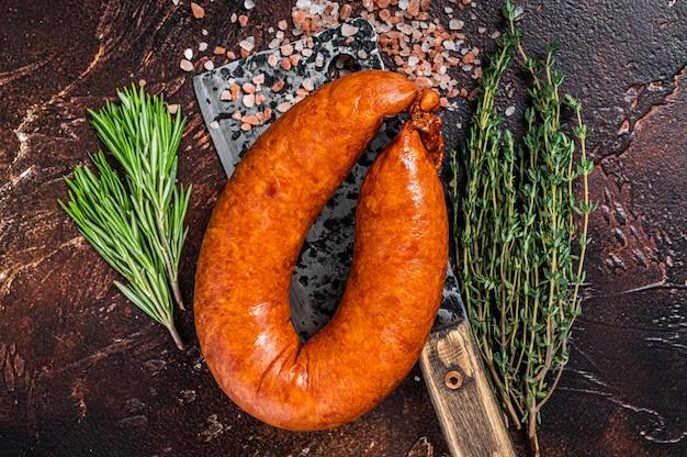 Saucisson fumé à chaud sur un couperet rustique de boucher aux herbes. fond sombre. vue de dessus.