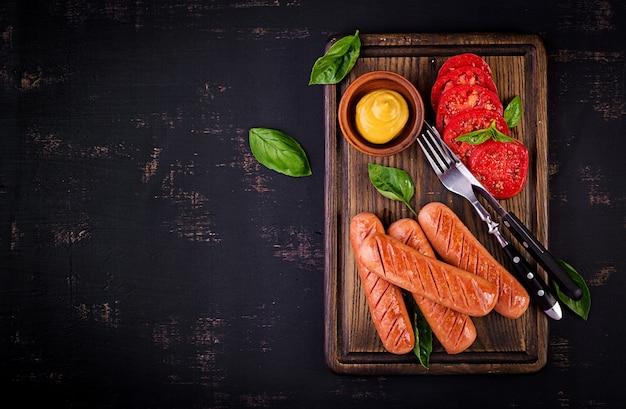 Saucisson grillé avec tomates, salade au basilic et oignons rouges