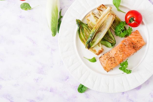 Saumon au four aux herbes italiennes et garni de chicorée. vue de dessus.