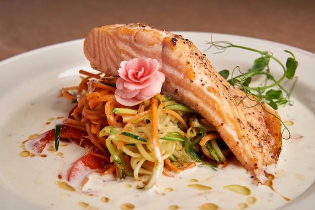 Saumon au four avec sauce à la crème sur un espace sombre, légumes finement hachés, vue de dessus. saumon florentin