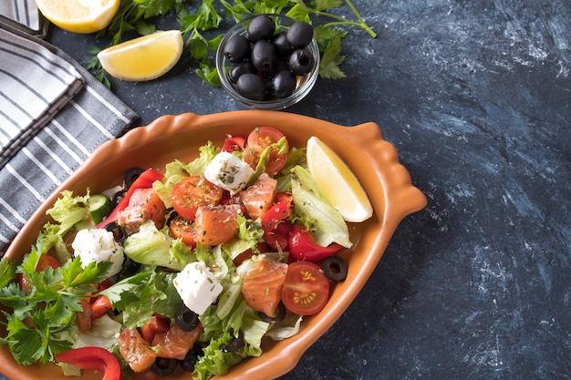 Saumon aux légumes, fromage et olives noires dans une assiette. nourriture diététique.