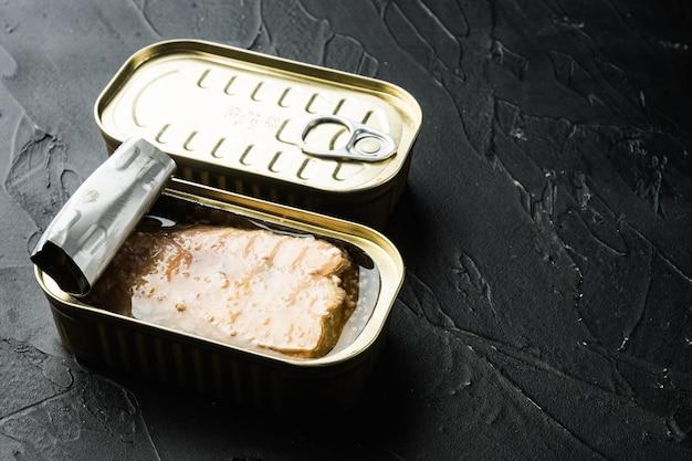 Saumon en conserve, conserves de poisson, en boîte de conserve, sur fond noir, avec fond et espace pour le texte