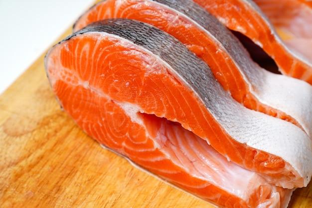 Saumon coupé en morceaux sur une planche à découper en bois. poisson rouge. truite fraîche pour la cuisson.