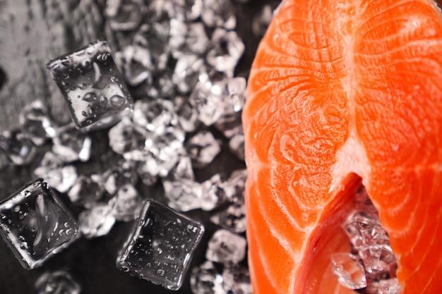 Saumon coupé en morceaux sur une planche en pierre noire avec des glaçons. poisson rouge. truite fraîche pour la cuisson.