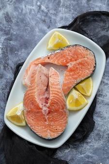 Saumon cru au citron sur un plat blanc sur fond de céramique