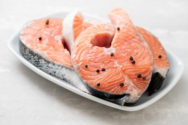 Saumon cru au poivre noir sur plat blanc sur fond en céramique