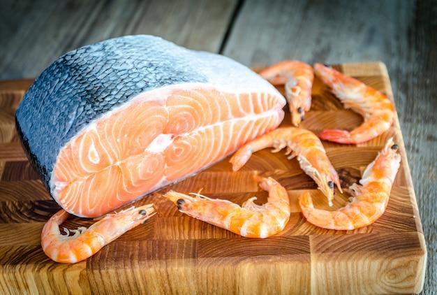 Saumon cru et crevettes sur la planche de bois