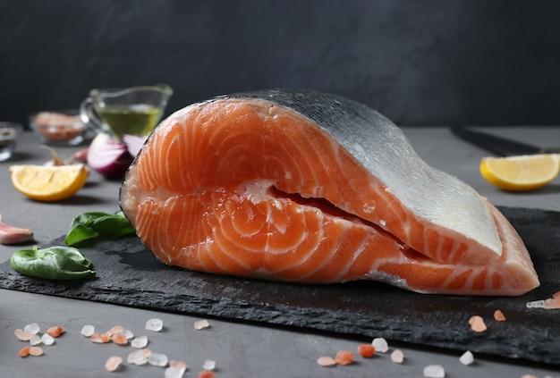 Saumon cru frais avec des ingrédients sur une ardoise sur une table sombre. fermer. format horizontal
