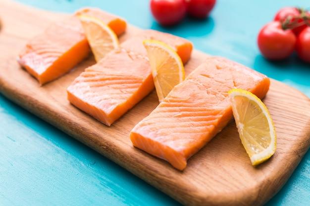 Saumon cru frais sur une planche à découper en bois.