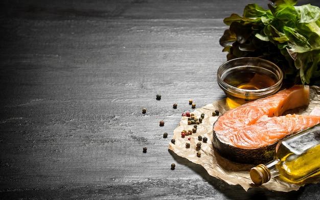 Saumon cru avec de l'huile d'olive, des épices et des herbes sur le tableau noir.