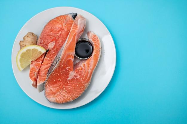 Saumon frais au citron, gingembre et sauce soja sur plaque blanche