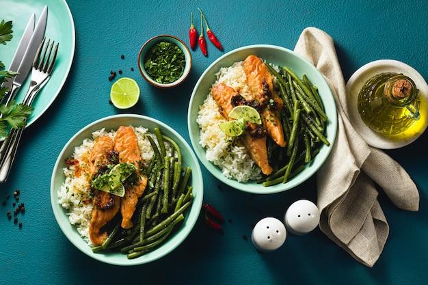 Saumon frais frit au gingembre et à l'ail dans du lait de coco, avec du riz basmati et des haricots verts dans des assiettes sur la table. recette saine pour toute la famille.