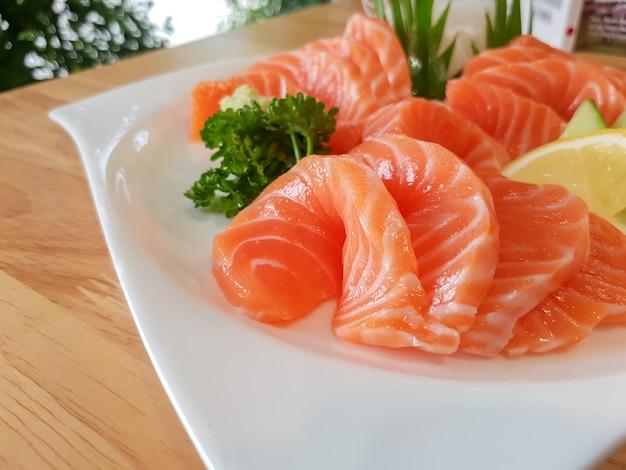 Saumon frais tranché dans un plat blanc.