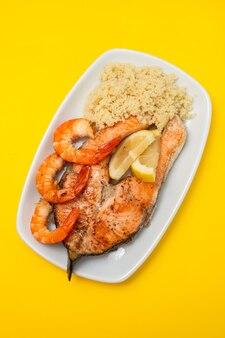 Saumon frit aux crevettes et cous-cous sur plat blanc