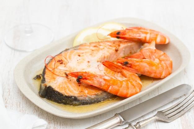 Saumon frit aux crevettes sur plat blanc sur une surface en bois