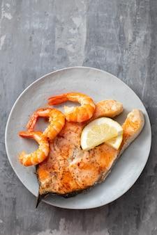 Saumon frit aux crevettes sur plat blanc sur table en céramique