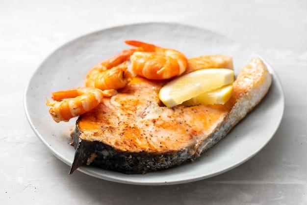 Saumon frit aux crevettes sur plat blanc