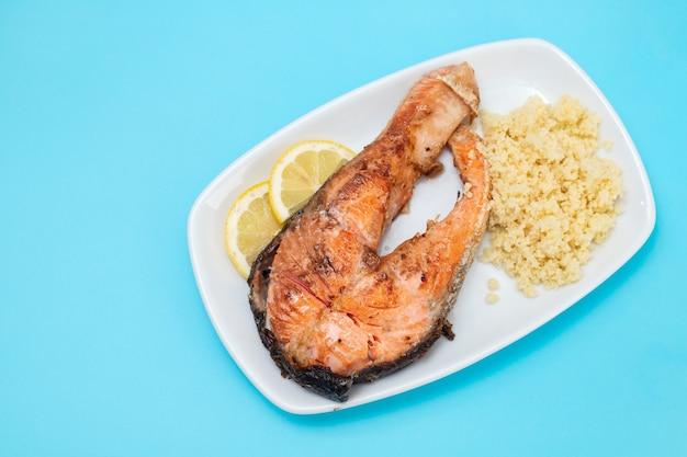 Saumon frit avec cous-cous sur plat blanc sur table bleue