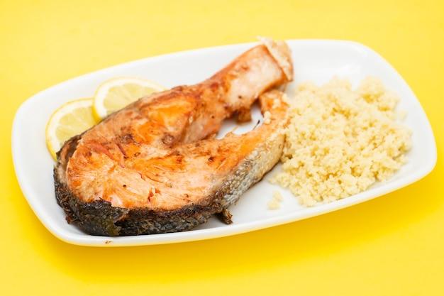Saumon frit avec couscous et citron sur plat blanc