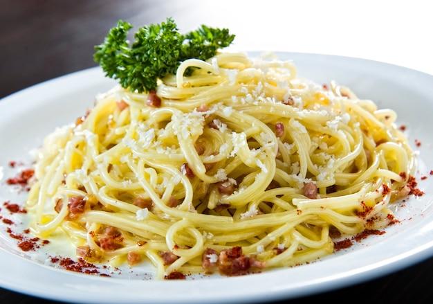 Saumon frit italien et penne rigate avec sauce crémeuse aux épinards et aux alfredo