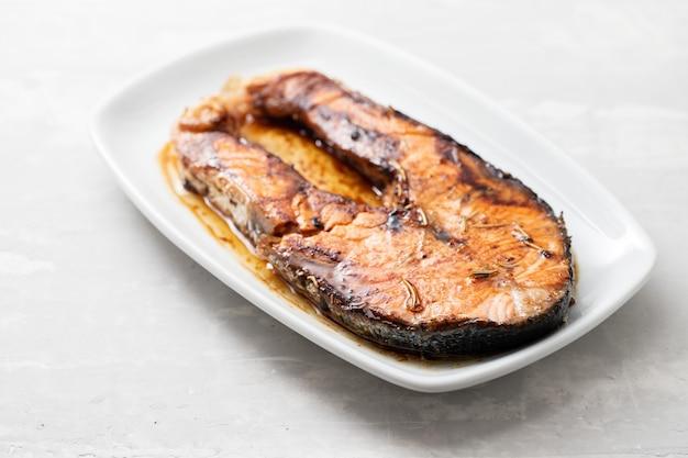 Saumon frit sur un plat blanc sur fond en céramique