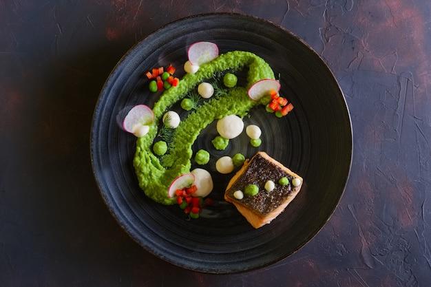 Saumon frit avec purée de pois décorée de radis et de pois