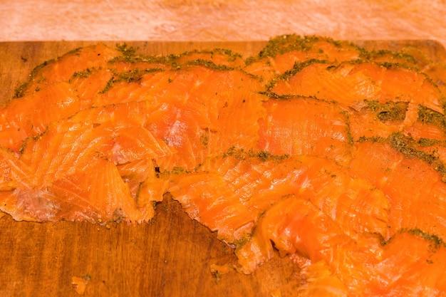 Saumon fumé artisanal recouvert d'aneth et d'épices sur une planche en bois.