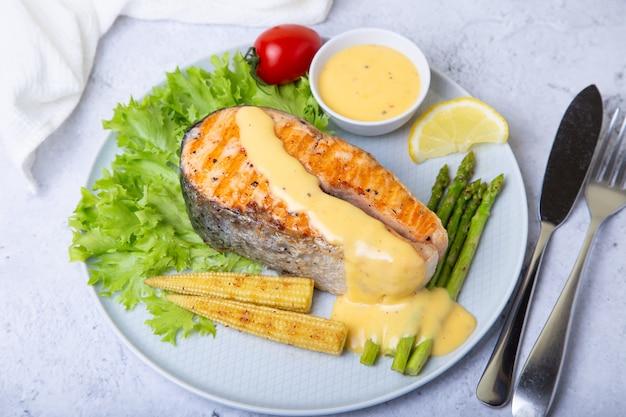 Saumon grillé aux asperges, mini maïs et sauce hollandaise. fermer.