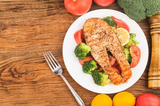 Saumon grillé avec divers légumes sur une assiette