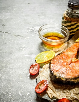 Saumon grillé à l'huile d'olive, tomates, citron et épices. sur la table en pierre.