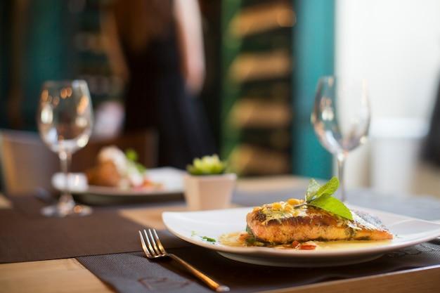 Saumon grillé avec sauce et herbes servies au restaurant