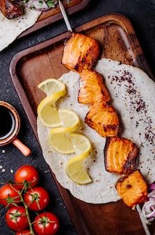 Saumon grillé servi dans du pain lavash avec des tranches de citron.