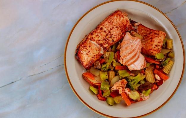Saumon et légumes cuits à la vapeur sur assiette. vue de dessus. copiez l'espace.